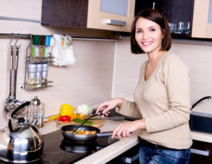 The joyful beautiful woman is on the kitchen prepares to eat